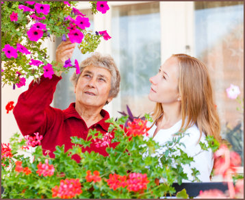 caregiver and elderly woman smelling the flowers