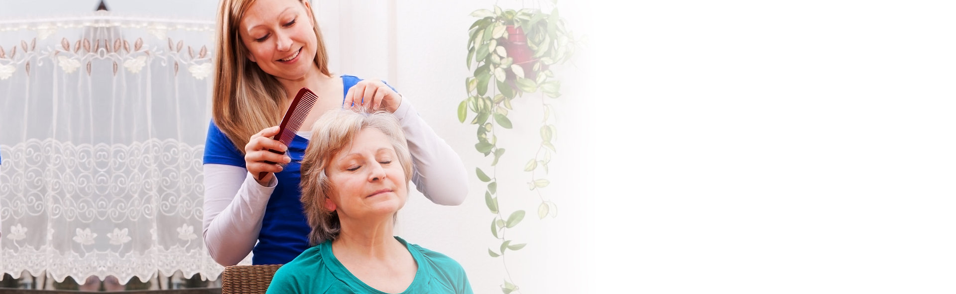 caregiver grooming the hair of an elderly woman