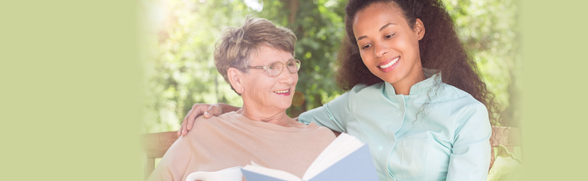 Senior women and caregiver reading book in the garden