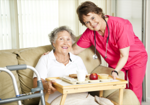 nurse serving food to an elderly woman